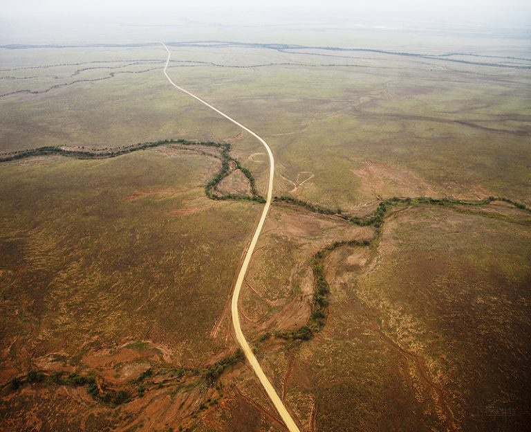 Helicopter aerial of the Road from Quilpie to Birdsville - after rain, a sheen of green appeared in the landscape. A rare sight. By Robyn Hills Photography, Australia